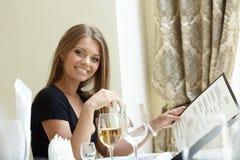 Sexy Frau, die mit Menü an der Mittagspause aufwirft Stockfoto