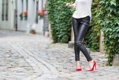 Sexy Frau, die rote Schuhe des hohen Absatzes in der Stadt trägt Stockfotografie
