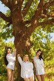 Sexy Frau drei im Hemd, das nahe einem großen Baum steht Lizenzfreie Stockbilder