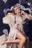 Sexy Frau im beige Seidenkleid, das auf dem schwarzen Lehnsessel sitzt Stockbild
