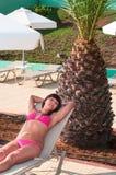 Sexy Frau im Bikini, der auf Aufenthaltsraum unter Palme legt lizenzfreies stockfoto
