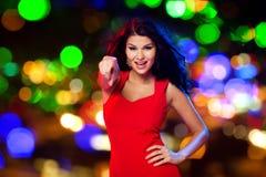 Sexy Frau im rotem Zeigen auf Sie auf Nachtklub Stockbilder