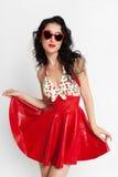 Sexy Frau im roten Latexkleid mit Sonnenbrille Stockbild