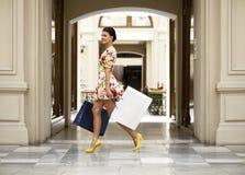 Sexy Frau im weißen Kleid blüht das Gehen in den Shop Stockbild