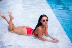 Sexy Frau legend und nahe Pool an der kühlen schwarzen modernen Sonnenbrille, BHbikiniwannen, glühende Hautfrau der Sonnenbräune  Lizenzfreies Stockbild