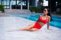 Sexy Frau legend und nahe Pool an der kühlen schwarzen modernen Sonnenbrille, BHbikiniwannen, glühende Hautfrau der Sonnenbräune  Stockfotos