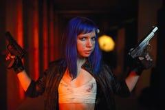 Sexy Frau mit dem blauen Haar, das zwei Gewehre hält und als Mörder schaut Lizenzfreie Stockfotos