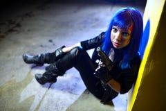 Sexy Frau mit dem blauen Haar, das zwei Gewehre hält und als Mörder schaut Stockfoto