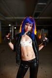 Sexy Frau mit dem blauen Haar, das zwei Gewehre hält und als Mörder schaut Lizenzfreies Stockbild