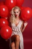 Sexy Frau mit dem blonden gelockten Haar trägt das elegante Kleid und hält viele roten Luftballone Stockbilder