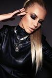 Sexy Frau mit dem blonden Haar in der Lederjacke und in der Halskette Stockfoto
