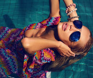 Sexy Frau mit dem blonden Haar in der Sonnenbrille im Swimmingpool Lizenzfreies Stockbild