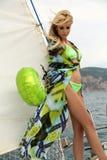 Sexy Frau mit dem blonden Haar im eleganten Badeanzug, der auf Yacht aufwirft Stockfotos