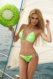 Sexy Frau mit dem blonden Haar im eleganten Badeanzug, der auf Yacht aufwirft Stockbild
