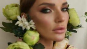 Sexy Frau mit dem dunklen Haar mit Abendmake-up mit den Blumen, die auf Kamera flirten stock footage