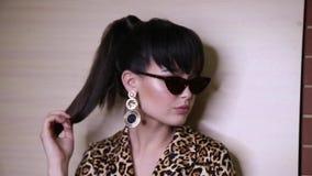 Sexy Frau mit dem dunklen Haar mit Abendmake-up in der eleganten Kleidung und in der Sonnenbrille, die auf Kamera flirtet stock video footage