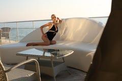 Sexy Frau mit dem langen blonden Haar, das eleganten schwarzen Badeanzug trägt Lizenzfreie Stockfotos