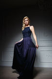 Sexy Frau mit dem langen blonden Haar im dunkelblauen Kleid Stockbild