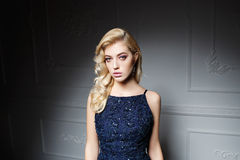 Sexy Frau mit dem langen blonden Haar im dunkelblauen Kleid Stockfotos