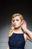 Sexy Frau mit dem langen blonden Haar im dunkelblauen Kleid Stockbilder