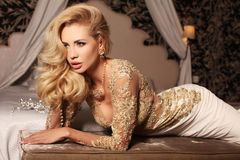 Sexy Frau mit dem langen blonden Haar trägt luxurios Spitzehochzeitskleid und -Juwel lizenzfreies stockbild