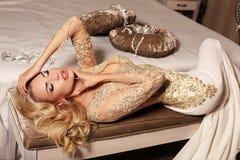 Sexy Frau mit dem langen blonden Haar trägt luxurios Spitzehochzeitskleid und -Juwel Lizenzfreies Stockfoto