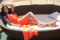 Sexy Frau mit dem schwarzen Haar in eleganten orange dressand Schuhen Lizenzfreie Stockfotografie
