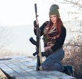 Sexy Frau mit einem Gewehr draußen Stockbilder