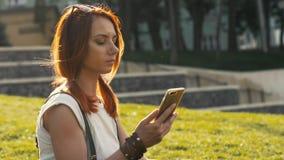 Sexy Frau mit roter Haarholding und Handy auf Sommer parken lizenzfreies stockfoto
