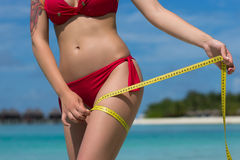 Sexy Frau am Strand im Bikini mit Maßband Das Konzept lizenzfreies stockbild