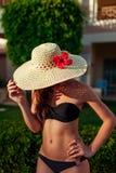 Sexy Frau in versteckendem Gesicht des schwarzen Bikinis mit Hut im Hotelgarten Sommerferien auf Erholungsort stockfoto