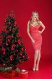 Sexy Frauen blond im roten Kleid nahe dem Weihnachtsbaum Stockbild