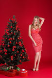 Sexy Frauen blond im roten Kleid nahe dem Weihnachtsbaum Stockfotografie