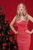 Sexy Frauen blond im roten Kleid nahe dem Weihnachtsbaum Lizenzfreie Stockfotografie
