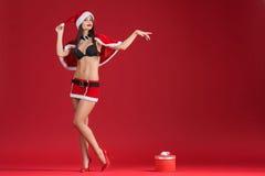 Sexy Frauen in der Kleidung von Santa Claus mit Weihnachtsgeschenk Stockbild