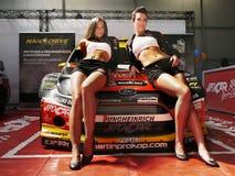 Sexy Frauen-Modelle auf Rennwagen lizenzfreies stockbild