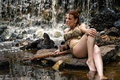 Sexy Frauenbogenschütze, der auf Felsen liegt Lizenzfreie Stockfotografie