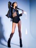 Sexy Frauenmodell kleidete Punk, das Wet look und warf im Studio auf Stockfotos