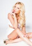 Sexy Frauenmodell mit den langen Beinen kleidete in der weißen Aufstellung gegen die Wand an Stockfotografie