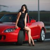 Sexy Frauenporträt der attraktiven Schönheit mit Auto Stockfoto