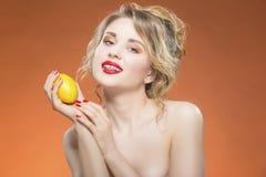 Sexy Frucht-Reihe Nacktes kaukasisches blondes Mädchen, das mit gelber Zitrone aufwirft Stockbild