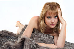 Sexy fur. Sexy blond woman laying on fur Royalty Free Stock Photos