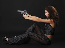 Sexy gangster shooting a handgun. Pretty woman is firing a handgun in the sitting position on the dark background. She is wearing tight trousers and stripy Royalty Free Stock Photo