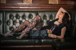 Sexy garter tights woman lying and drinking cocktail in pub Royalty Free Stock Photo