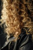 Sexy gekräuseltes blondes Haar der Nahaufnahme im Studio mit dunklem Hintergrund stockfotografie