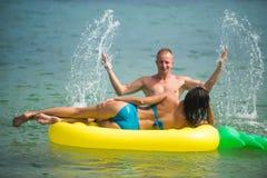 Sexy gelukkig paar op Caraïbische overzees Ananas opblaasbare matras, activiteitenvreugde Het strandwater van de Maldiven of van  royalty-vrije stock foto's