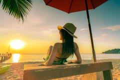Sexy, geniet en ontspan van de bikini van de vrouwenslijtage liggend en het zonnebaden sunbed bij zandstrand bij paradijs tropisc stock afbeeldingen