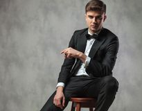 Sexy gentleman dressed elegantly sitting and pointing to side Royalty Free Stock Photo