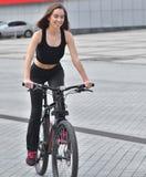 Sexy geschiktheid Jonge mooie vrouw in het zwarte sportslijtage stellen openlucht op de fiets bij het stadion stock foto