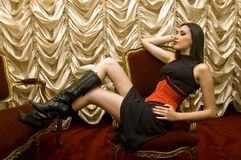 Sexy girl. Beautiful brunette with leather boots seated in armchair Stock Photo